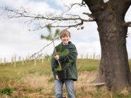 Garçon tenant jeune arbre — Photo de stock