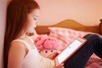 Fille utilisant une tablette numérique dans la chambre à coucher — Photo de stock