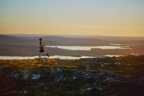 Trailrunning-Mann auf Klippe bei Sonnenuntergang, Keimiotunturi, Lappland, Finnland — Stockfoto