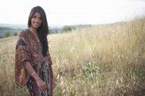 Donna in posa per la fotocamera in piedi sul campo — Foto stock