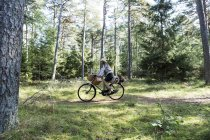 Mature woman cycling with foraging baskets in forest — Stock Photo