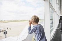Garçon regarde par la fenêtre de l'aéroport à piste — Photo de stock