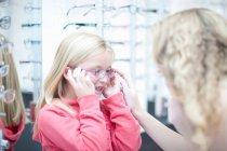 Молодая девушка примеряет очки — стоковое фото