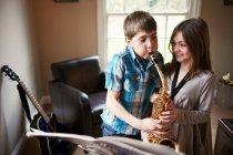 Діти грають з саксофоном — стокове фото