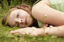 Крупный план портрета девушки, лежащей на траве — стоковое фото