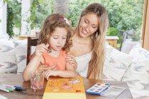Madre e hija pintando en la mesa - foto de stock