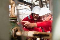 Рабочие, осматривающие оборудование на месте — стоковое фото