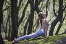 Женщина на скале, опираясь на руки протягивать — стоковое фото