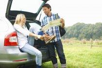 Coppia in auto mappa lettura preparazione per l'avventura escursionistica — Foto stock