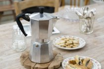 Stove top coffee pot with plates of baked good on dining table — Stock Photo