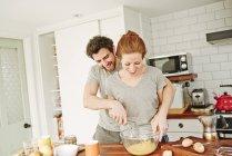 Взрослая пара, взбивающая яйца вместе за кухонным столом на завтрак — стоковое фото