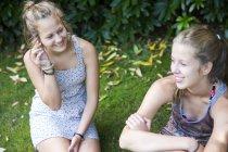 Two teenage girls sitting in garden — Stock Photo