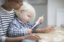 Boy using scissors to cut paper with his mother — Stock Photo