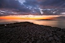 Sole che tramonta sulle formazioni rocciose spiaggia — Foto stock