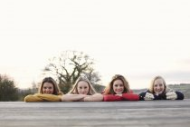 Four teenage girls in a row on patio — Stock Photo