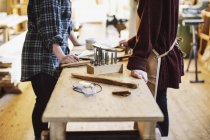 Cropped view of two craftswomen at workbench in pipe organ workshop — Stock Photo
