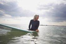 Старший жінка, сидячи на дошку для серфінгу в море — стокове фото