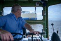 Буксир капітана керма, дивлячись на плече, щоб судно на морі — стокове фото