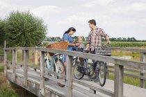Famille à bicyclette sur pont en bois, arrêtée pour boire — Photo de stock