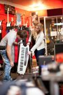 Couple looking at keytar in music store — Stock Photo