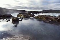 Roches dans l'eau des chutes d'eau et ciel nuageux — Photo de stock
