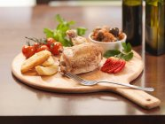 Chicken and fruit on wooden board — Stock Photo