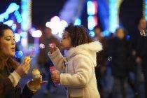 Мати і дочка дует бульбашки, в парк атракціонів — стокове фото