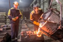 Workers pouring molten metal into moulds in foundry — Stock Photo