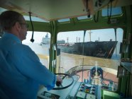 Captain steering in bridge of tugboat towing ship at sea — Stock Photo