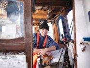 Fisherman in wheelhouse of fishing boat — Stock Photo