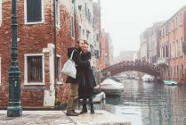 Couple hugging on misty canal waterfront, Venice, Italy — Stock Photo