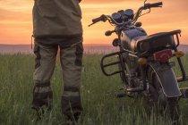 Vue arrière de l'homme debout dans le champ à côté de la moto — Photo de stock