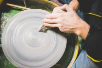 Overhead view of mid adult mans hands cleaning pottery wheel — Stock Photo