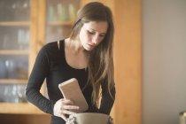 Jeune femme à la maison, en regardant dans le sac à main — Photo de stock