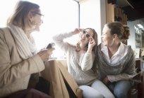 Семья из трех поколений примеряет солнечные очки в магазине — стоковое фото