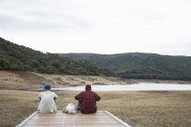 Vue arrière de jeunes hommes assis sur une jetée en bois regardant une chaîne de montagnes, Nuoro, Sardaigne, Italie — Photo de stock