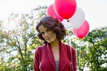 Жінка, що перевозять повітряні кульки на відкритому повітрі, Зосередьтеся на передньому плані — стокове фото