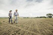 Мужчина фермер и подросток, идущий по вспаханному полю — стоковое фото