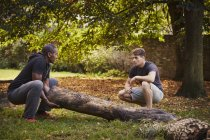 Personal trainer showing young man how to lift tree trunk in park — Stock Photo