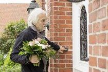 Homme âgé avec bouquet sonnerie sonnette — Photo de stock