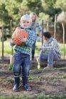 Ragazzo che porta zucca in giardino — Foto stock
