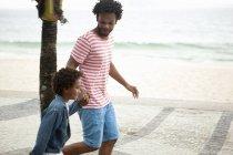 Батько і син працює рука об руку на пляж Іпанема, Ріо-де-Жанейро, Бразилія — стокове фото