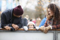 Girl with parents peeking over barrier, looking at camera smiling — Stock Photo