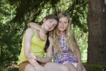 Підлітки сидять в саду з рукою навколо — стокове фото