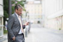 Uomo d'affari maturo, lettura di testi su smartphone sulla strada — Foto stock