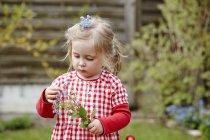 Petite fille portant une robe gingham tenant des fleurs — Photo de stock