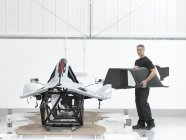Engineer with part assembled  supercar in car factory — Stock Photo