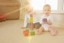 Niños jugando con juguetes en el suelo - foto de stock