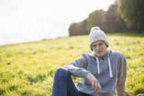Портрет молодого человека, сидя на траве носить шапка — стоковое фото