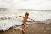 Мальчик играет волнами на пляже — стоковое фото